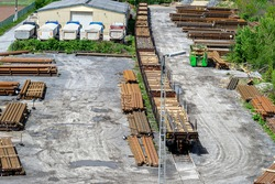 Long and thick, rust-covered steel bars stacked outside on a gravel square, visible railroad tracks and wagons, viewed from above.