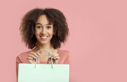 Long-awaited purchase, shopping with pleasure, gifts for holiday. Happy excited millennial african american curly woman holds light paper bag with blank space, isolated on pink background, studio shot