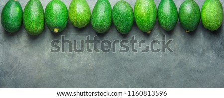 Long Banner Header. Bunch of Ripe Raw Avocados Arranged in Upper Border on Dark Stone Background. Top View Copy Space. Healthy Lifestyle Vitamins Oil. Mediterranean Cuisine Concept. Poster Template #1160813596