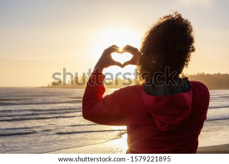 Photo of  Long Beach, Near Tofino and Ucluelet in Vancouver Island, BC, Canada. Adventurous Girl making Hearth Shape with Hands with golden sunset on the Pacific Ocean Coast in the background.