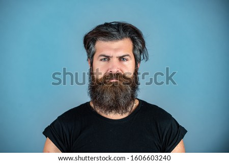 Long beard. Perfect beard. Close-up of young bearded man standing against blue background.