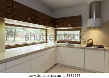 Long beige counter top in modern kitchen interior