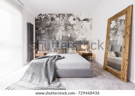 Long blanket lying on a double bed in a rectangular, monochromatic bedroom with a radiator next to a window with blinds #729468436