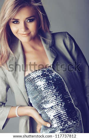long blond hair beautiful woman in silver sequin dress on studio background