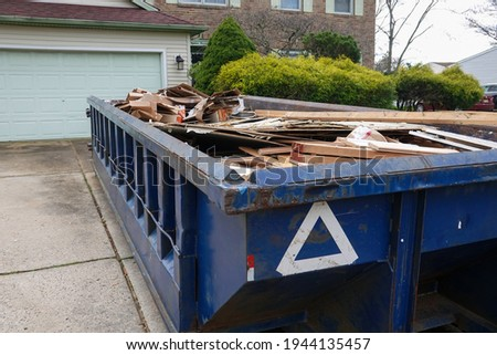 Long blue dumpster full of wood and other debris in the driveway in front of a house in the suburbs Сток-фото ©