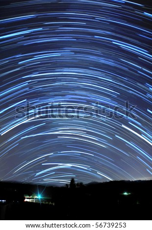 Long blue star trails in the sky above a mountain.