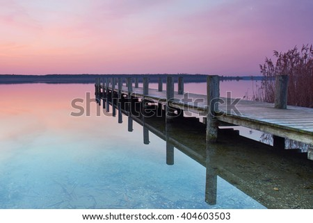 long boardwalk on the lake in the evening at sunset, silent and light