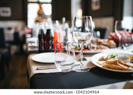 Long brown table served with white dishes with delicious food stands in the hall