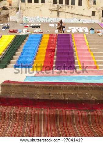 long colorful cloth laying to dry on the ghats at the Ganges river in Varanasi, India