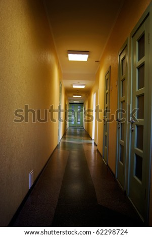 Long corridor in hospital with doors and chairs