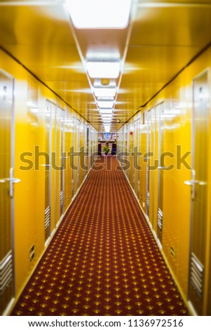 Long corridor of cruise ship, yellow and brown walls and doors