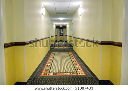 Long corridor with a window in modern hotel showing patterned carpet