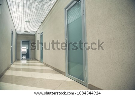 Long corridor with different entries, bright light from lamps and striped floor #1084544924