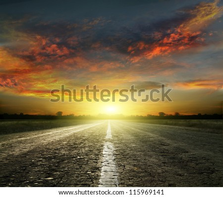 Long country road with white lines down the centre stretching off past a lone tree to the distant horizon - stock photo