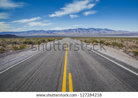 Long desert highway to the mountains under the hot sun