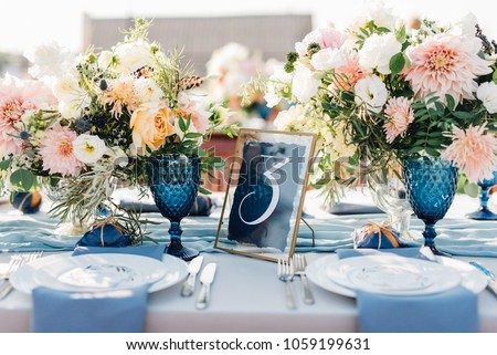 Long dinner tables covered with white cloth, served with porcelain and blue glasses and rich decorated with flowers stand on the roof of a house