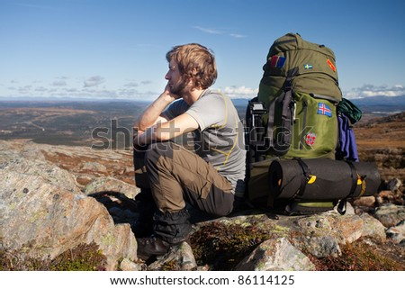 Long distance hiker have a break on the top of the mountain