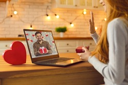 Long-distance relationship and virtual date in lockdown. Young couple in love video calling each other during quarantine and showing gifts and presents they prepared for Saint Valentine's Day