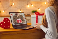 Long-distance relationship and virtual date in quarantine. Faceless anonymous couple in love video calling each other during lockdown and showing anniversary gifts or Valentine presents they prepared