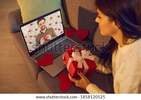 Long-distance relationship. Happy young couple talking and sending each other love on virtual date on Valentine's Day. Happy woman video calling man during lockdown and showing present she prepared