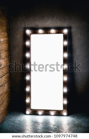 Long dressing mirror with light bulbs stands on the floor against a wooden and concrete wall in loft style room. with white background. place for text #1097974748