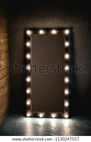 Long dressing mirror with light bulbs stands on the floor against a wooden and concrete wall in loft style room. with brown background. place for text  #1130247557