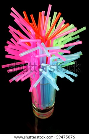 long drink glass with some water and many colored plastic straws symbolizing water global shortage