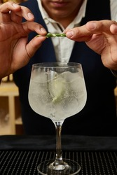 Long drink, sweet yellow transparent and white drink with pineapple decoration. Preparation of a drink with white drink, alcohol, liquor. Bartender's hands.