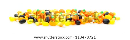 Long edge or border of assorted Halloween candy over white