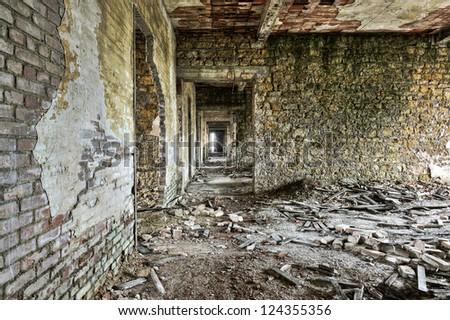 Long empty corridor and doors in abandoned building - stock photo