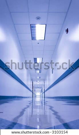 Long, empty corridor in a hospital or office building, with the ceiling lights reflected on the shiny floor. Image naturally almost monochromatic, bluish tint suggesting a cold, sterile environment