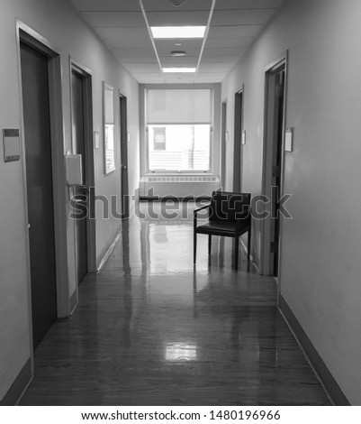 long empty hallway with a empty lone chair in a hospital corridor