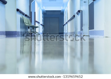 Long empty hallway with chairs in hospital. Tinted picture.