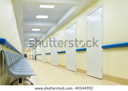 long empty yellow corridor with chairs in hospital