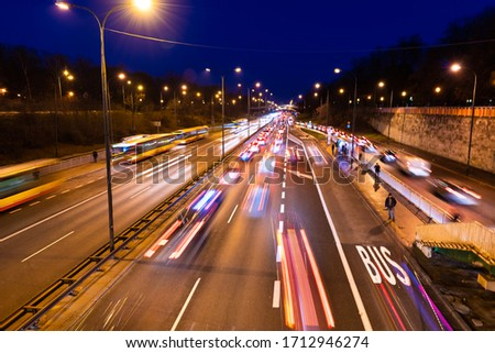 Long exposure above high angle aerial view of Aleja Armii Ludowej street in Warsaw, Poland at night with traffic cars, people standing at bus stop with light trails Zdjęcia stock ©
