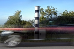 Long exposure at a speed measuring device and a fast passing car in motion blur, automatic traffic monitoring with light radar and camera to punish speeding with fines or revocation of driving license