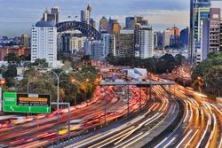 Long exposure blurred vehicle motion on multi-lane Warringah freeway going through North Sydney in Sydney, Australia. Headlights during rush hour commute towards Sydney harbour bridge and CBD towers.