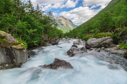 Long exposure flowing rapid mountain river in norwegian sunny valley