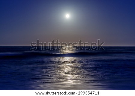Long exposure, full moon setting, with stars, moonbeam, seafoam, back dropped on a blue sky on Moonstone Beach, along the Big Sur Highway, on the California Central Coast, near Cambria CA.