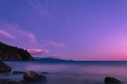 Long exposure image at sunset time from a coastal area in the Mediterranean region of Turkey. Some irregular rocks in the foreground, hills and mountain ranges in the background.