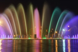 Long exposure image of colorful fountain sprays in blue, green, pink neon illumination. Water rainbow. Bright night in the Gorky Park in Moscow. High resolution photo.