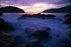 Long exposure image of Dramatic sky seascape with rocks in the foreground sunset or sunrise scenery background