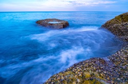 Long exposure image of Dramatic sky seascape with rocks in the foreground sunset or sunrise scenery background Beautiful light of nature amazing landscape.