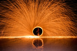Long exposure image of The man dancing swing fire Show on the beach in the Island of Thailand.