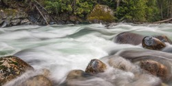 long exposure landscape image of Halfway River hot springs near Nakusp, British Columbia. silky smooth water rushing over big rocks and boulders.