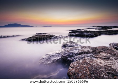 Long exposure landscape photo of sea with rocks during sunset. Milky smooth water.  #1503966596