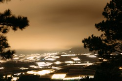Long-exposure landscape photo of the illuminated greenhouses and farms at the countryside of Dalat, Vietnam. The fog covered mountains background and dreamy lights give the scene a peaceful feels.