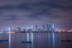 Long exposure landscape shot of Mumbai city at night from bandra reclamation with soft Focus. Reflection of lights in water.  Cityscape of urban city in India. Room for text. Copy Scape.