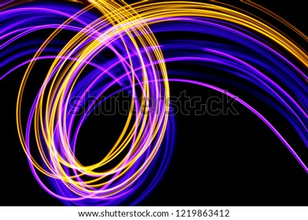Long exposure, light painting photography.  Neon pink purple and metallic yellow gold vibrant curves and loops of color, curving and wavy lines against a black background #1219863412