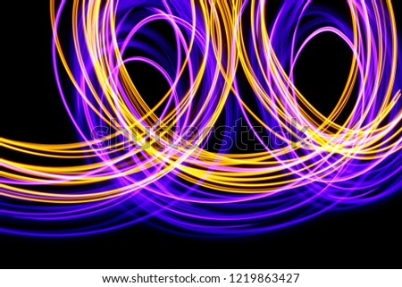 Long exposure, light painting photography.  Neon pink purple and metallic yellow gold vibrant curves and loops of color, curving and wavy lines against a black background #1219863427